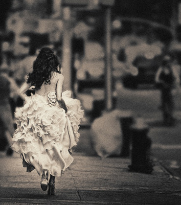 Sepia tone photograph of a bride walking away.