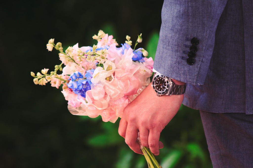 groom wearing a watch and holding brides flowers in left hand