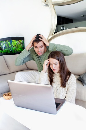 young couple confused in front of computer